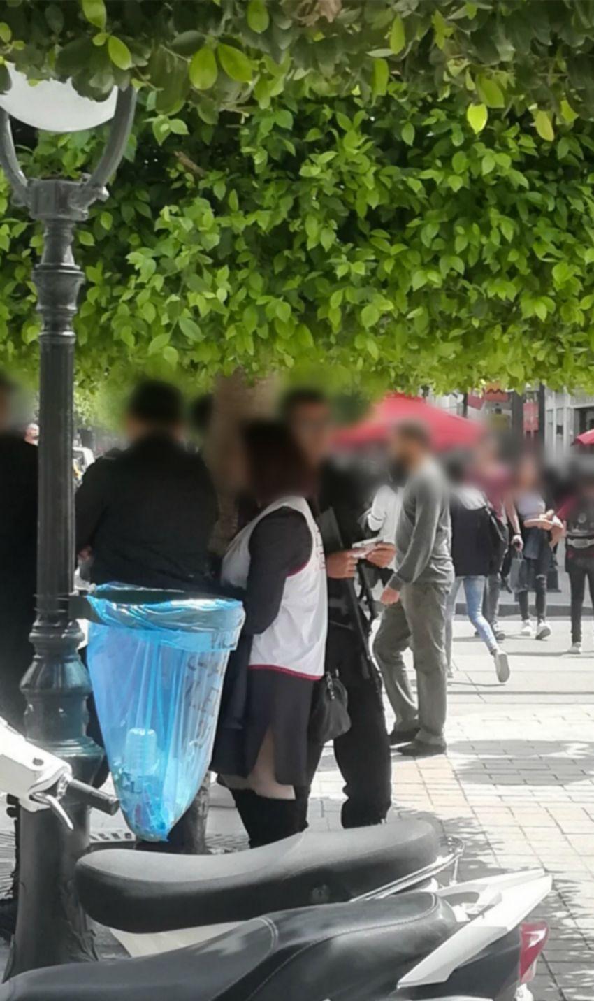الصورة من زاوية أقرب حيث نرى الأمني يحمل مطوية للحملة الانتخابية